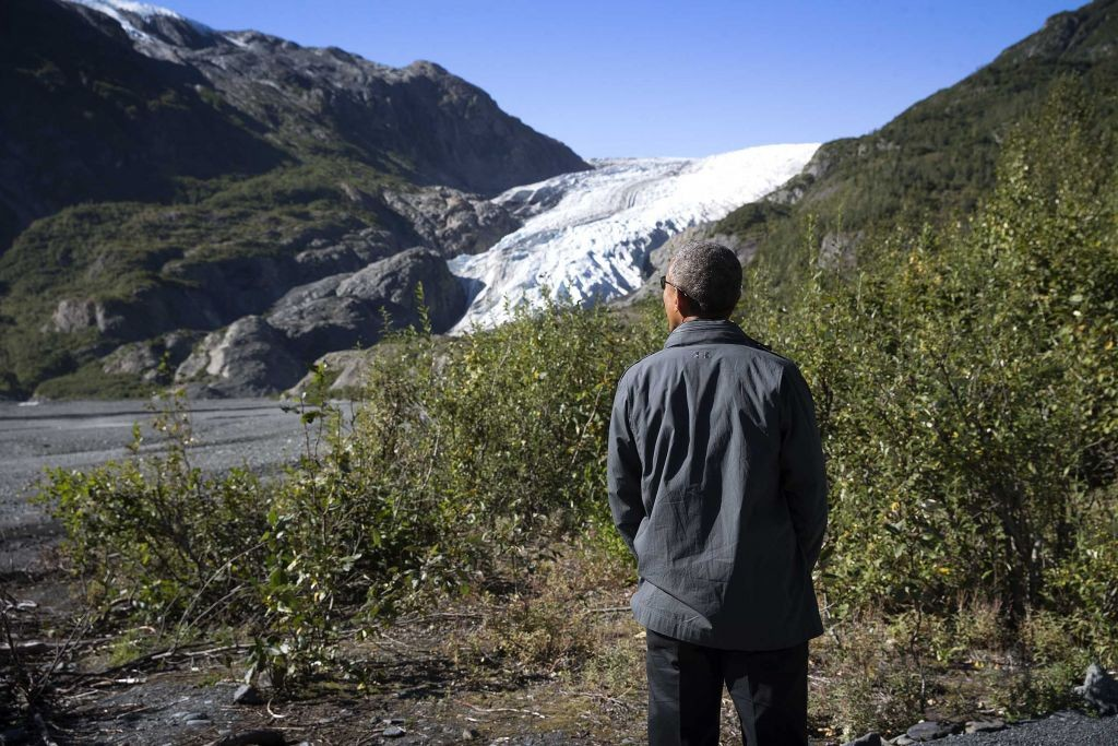 President Barack Obama looks over melting glacier