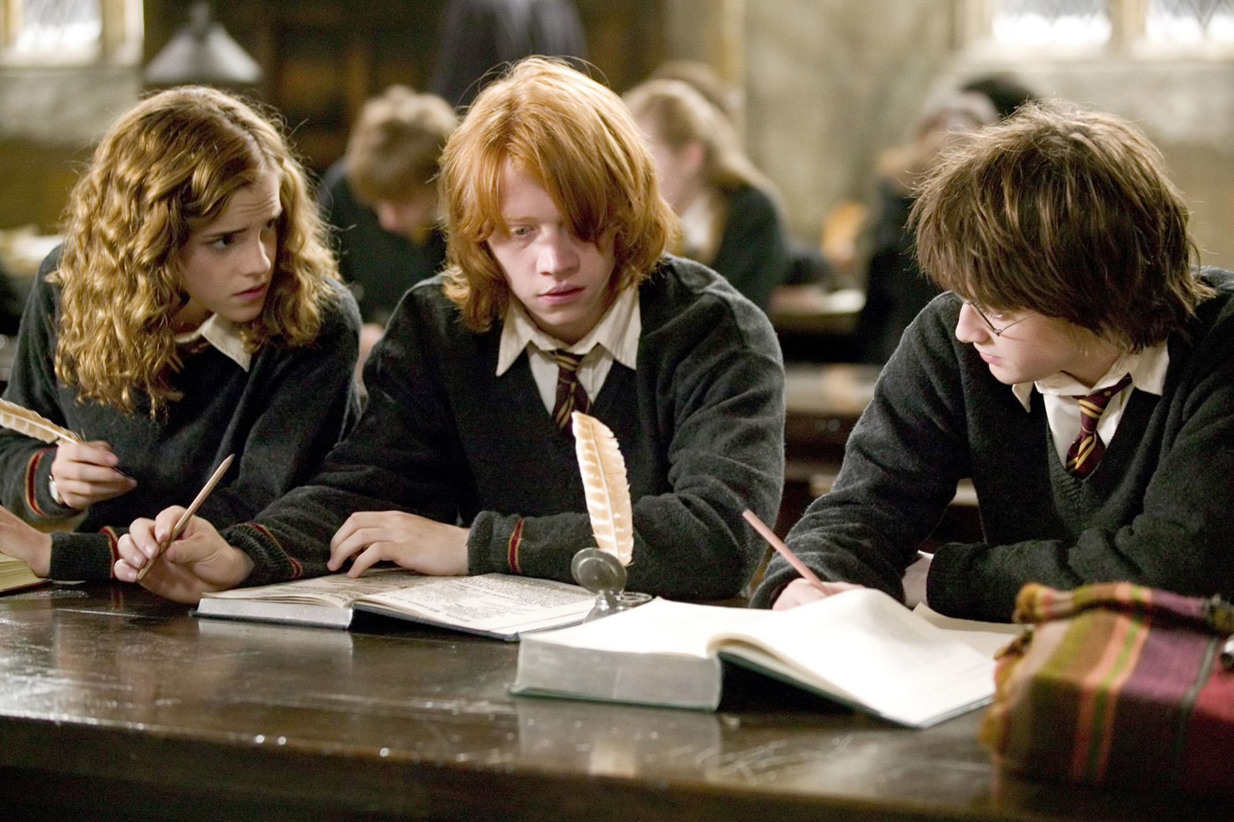 Hermione helps Ron and Harry with their homework